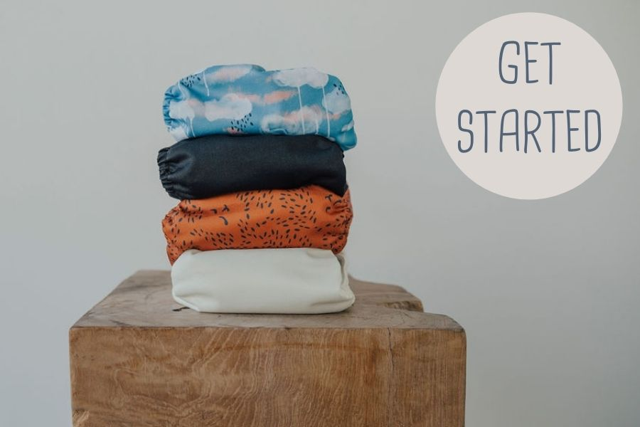 Four reusable nappies stacked on a wooden block - get started with reusable nappies